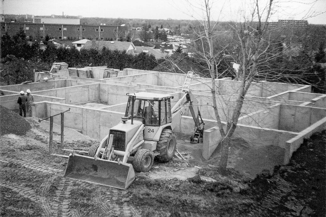 Photo of tractor on construction site. Construction of foundation/ground floor units at Zerin Place - an affordable housing development project in London Ontario